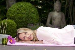 Blonde glückliche mittlere Greisin, die auf einer Decke im Zengarten liegt Lizenzfreies Stockbild