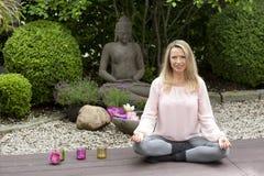 Blonde glückliche mittlere Greisin, die im Zengarten sitzt Lizenzfreies Stockbild