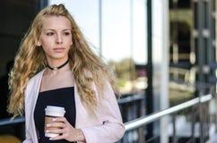 Blonde glückliche Studentengeschäftsfrau mit Kaffee auf der Straße Stockbild