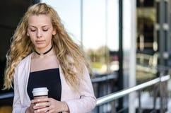 Blonde glückliche Studentengeschäftsfrau mit Kaffee auf der Straße Lizenzfreies Stockbild