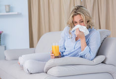 Blonde with glass of orange juice and sneezing Royalty Free Stock Image