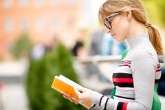 Blonde in glasses looks in book on summer Royalty Free Stock Photo