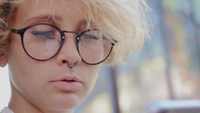 Blonde with glasses looks at the phone stock video footage