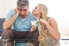 Blonde gold digger wife asking 100 Euro from husband. Blonde gold digger wife asking 100 Euro from sad husband, indoors royalty free stock images