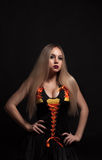 A Blonde gothic priestess in the dark. Stock Images