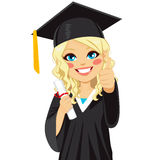 Blonde Graduation Girl. Beautiful blonde girl on graduation day with diploma and making thumbs up hand sign Royalty Free Stock Image