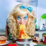 Blonde grappig op keuken die deegwaren als gek eet royalty-vrije stock foto