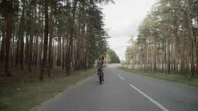 The blonde rides a bicycle. Beautiful young girl rides a bike on the highway. stock footage
