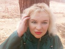 The blonde in green jacket with green eyes about tree of on the forest path in April. royalty free stock photo