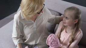 Blonde Großmutter, die zu Hause mit ihrer kleinen Enkelin, handgemacht strickt stock video footage