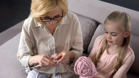 Blonde Großmutter, die zu Hause mit ihrer kleinen Enkelin, handgemacht strickt lizenzfreie stockfotografie