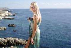 Blonde in groene pareo op rotsachtig strand dichtbij overzees Royalty-vrije Stock Afbeelding