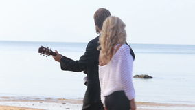 Blonde guitarist plays for blonde woman on beach stock footage