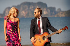 blonde and guitarist side-view against island Royalty Free Stock Photos