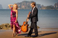 Blonde and guitarist side-view on beach Stock Photo