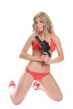 Blonde with a gun. Beautiful girl in red bikini with the big black gun isolated on white Royalty Free Stock Image