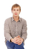 Blonde guy. Portrait of blonde guy in shirt and jeans sitting on white with hands over crossed legs Stock Photo