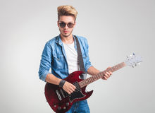 Blonde guy playing electric guitar while posing for the camera. Cool blonde guy playing electric guitar while posing for the camera in studio background Royalty Free Stock Photography