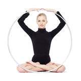 Blonde gymnast with hula hoop. Isolated portrait of beautiful young blonde woman gymnast sitting lotus pose with hula hoop Stock Photography