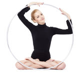 Blonde gymnast with hula hoop. Isolated portrait of beautiful young blonde woman gymnast training yoga exercise lotus pose with hula hoop Stock Photo