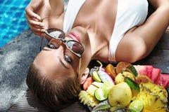 Blonde hübsche Dame, die ein Bündel exotische Frucht hält Lizenzfreies Stockbild