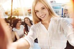 Blonde hübsche Frau, die bei den Freunden liegt Stockbild
