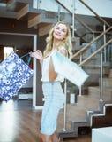 Blonde hübsche Frau, die Einkaufstaschen hält Lizenzfreies Stockfoto