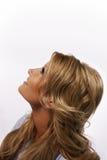 Blonde hübsche Frau, die oben schaut Stockbild