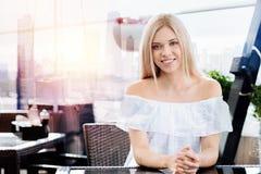 Blonde hübsche Frau, die zur Kamera lächelt Lizenzfreie Stockfotografie