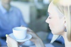 Blonde hübsche Frau sitzen bei Tisch vor Manngrifftasse kaffee Stockfotos