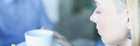 Blonde hübsche Frau sitzen bei Tisch vor Manngrifftasse kaffee Lizenzfreie Stockfotografie