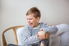 Blonde haar gelukkige jongen die die bij bank glimlachen op de witte achtergrond wordt geïsoleerd Royalty-vrije Stock Afbeeldingen
