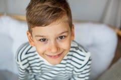 Blonde haar gelukkige jongen die die bij bank glimlachen op de witte achtergrond wordt geïsoleerd Stock Foto