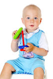 Blonde hair baby boy holds toy Stock Photo