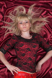 Blonde Hair. Beautiful girl lying on a red cloth Royalty Free Stock Images