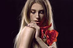 Blonde hair. Beautiful woman with red flower. Flower. stock photography