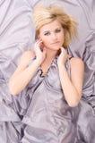 Blonde hair lying of grey silk Royalty Free Stock Image