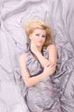 Blonde hair lying of grey silk Stock Images