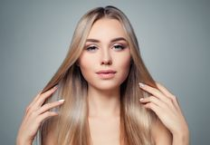 Blonde hair woman. Beautiful model girl with long straight healthy hairstyle. Haircare, hair styling and hair straightener concept