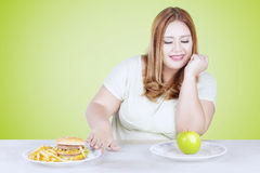 Blonde hair woman choosing apple. Portrait of blonde hair woman choosing a green apple rather than hamburger and french fries Stock Image