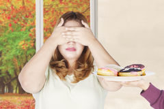 Blonde hair woman closed eyes for donuts. Portrait of blonde hair woman closed her eyes for a plate of donuts with autumn background on the window Royalty Free Stock Photography