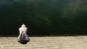 Blonde hair woman sitting by the dark river water, sad royalty free stock photos