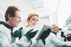 Blonde-haired biologist smiling watching photos from conference. Conference photos. Blonde-haired amicable biologist smiling while watching memorable photos from stock image