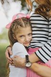 Blonde-haired blue-eyed appealing daughter hugging her parent stock images