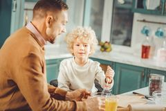 Curly blonde-haired boy helping his father in the kitchen. Blonde-haired boy. Curly blonde-haired boy wearing beige shirt helping his father in the kitchen royalty free stock photos