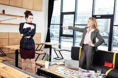 Blonde-haired businesswoman asking young secretary to go away stock photography