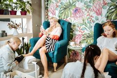 Blonde-haired businesswoman using her smartphone having pedicure. Using phone. Blonde-haired businesswoman using her smartphone having pedicure with her daughter stock image