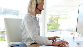 Blonde haired businesswoman working with a headset Royalty Free Stock Photos