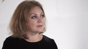 Blonde haired and grey eyed woman dressed in black is looking around calmly. Blonde haired woman at her 40s with wide open eyes is looking around calmly without stock footage