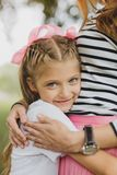 Blonde-haired mother wearing striped shirt hugging her cute girl royalty free stock images